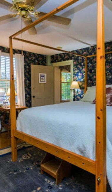 bedroom with dark blue floral wallpaper, 4-poster bed
