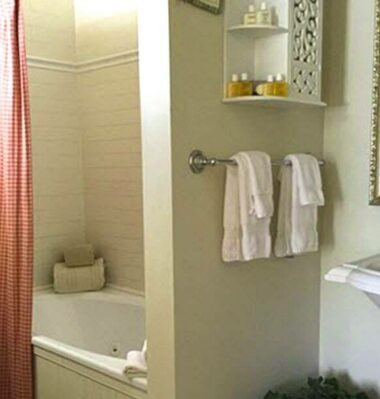 bathroom with red shower curtain, white towels, pedestal sink
