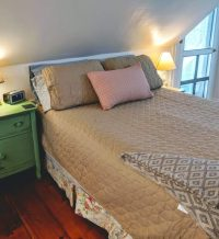 bed with brown bedspread next to green night table