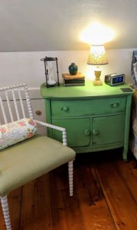 green night table next to bed and chair with green cushion