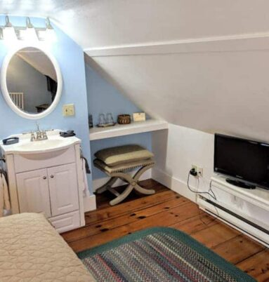 sink with mirror and TV on shelf