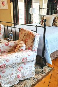 bedroom with iron bed, blue linens, two pink floral chairs