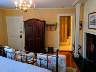 bedroom with iron bed, blue linens, two pink floral chairs, armoire