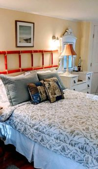 bedroom with red ladder over bed
