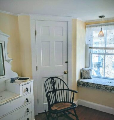 yellow room with white dresser, chair and window seat