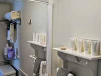 bathroom with shelf in front of mirror