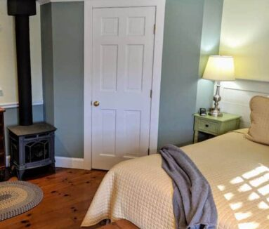 room with fireplace and bed with white linens