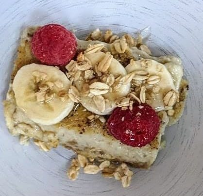 breakfast topped with bananas and raspberries