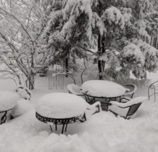 tables and chairs covered by snow