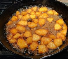 pineapples cooking in brown sugar in cast iron skillet