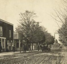 looking down dirt street with old buildings, horses and wagon