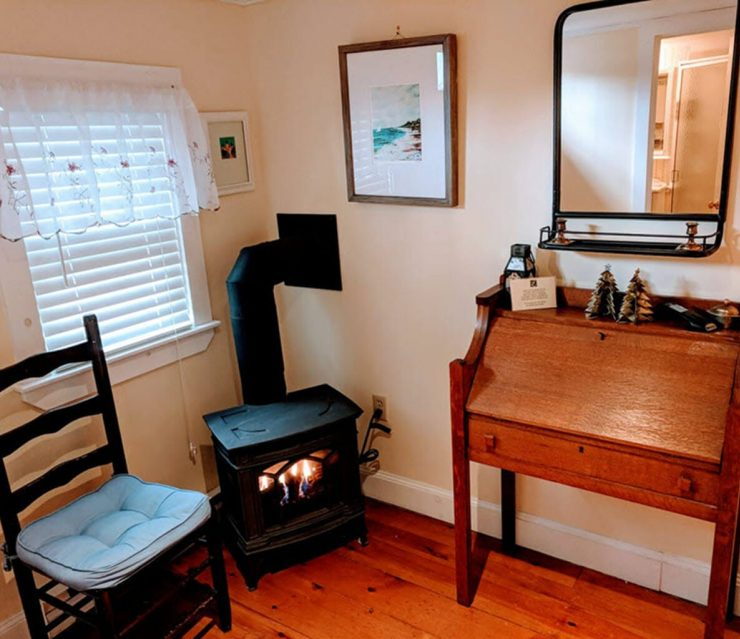 room with corner fireplace, desk and chair
